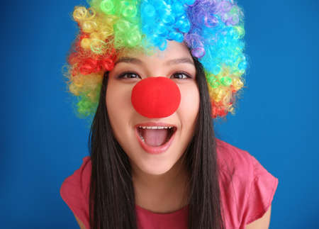 Young woman in funny disguise posing on color background. April fools day celebration
