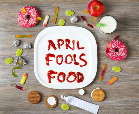Composition with phrase April fools food and treats on wooden background Stock Photo