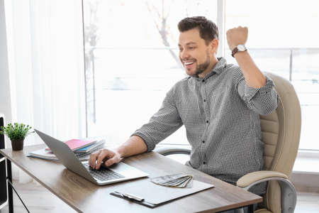 Happy businessman with laptop working at table in office