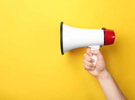 Man holding megaphone on color background