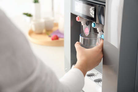 Woman filling glass from water cooler, closeup