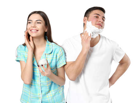 Young man shaving and his girlfriend applying face cream on light background