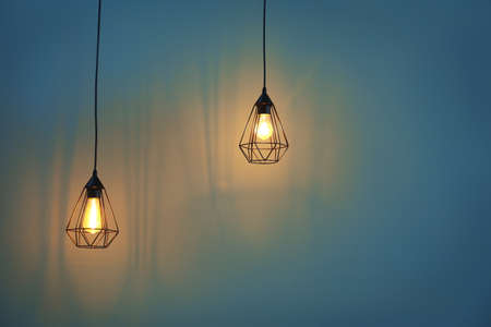 Elegant lamps hanging on color background Stock Photo