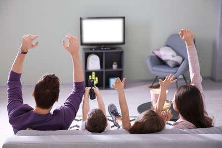Familie die op TV thuis op bank kijkt Stockfoto