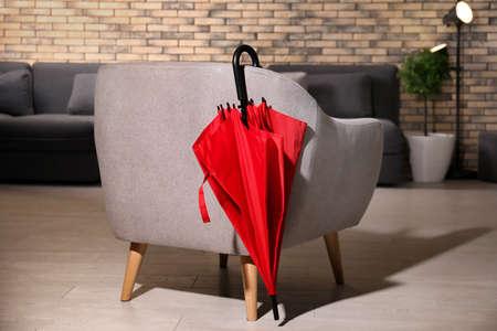 Stylish red umbrella near armchair indoors Stock Photo
