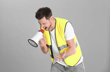 Worker with megaphone on grey background Stock Photo