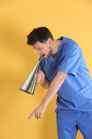 Male doctor with megaphone on color background