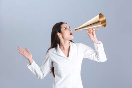 Female doctor with megaphone on grey background