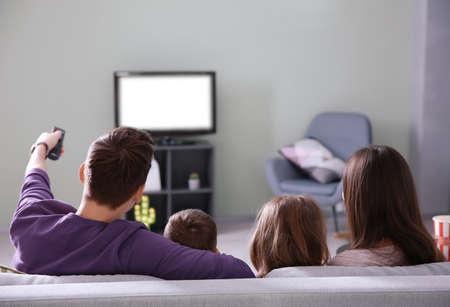 Familie die op TV thuis op bank kijkt
