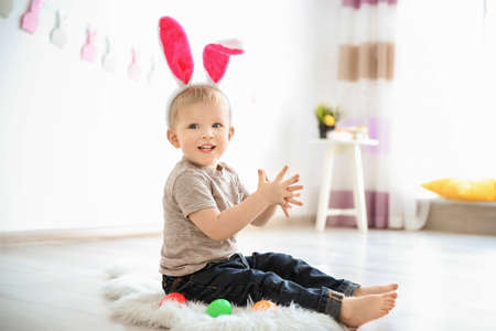 Cute little boy with bunny ears and Easter eggs indoors Stock Photo