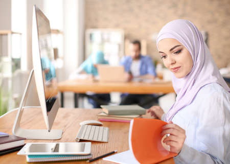 Muslim woman in traditional clothes studying indoors