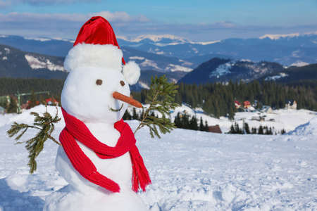 Snowman in Santa hat at mountain resort. Winter vacation