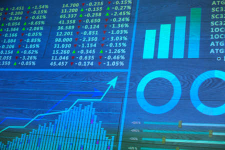 Projection of business presentation with stock market data on wooden surface. Forex concept Stock Photo