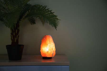 Himalayan salt lamp on wooden cabinet. Interior design element