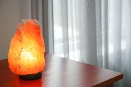 Himalayan salt lamp on wooden cabinet indoors