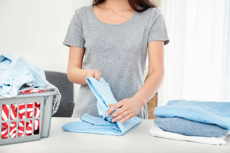 Woman folding freshly washed clothes at table indoors. Laundry day