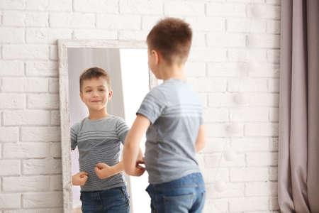 Ładny mały chłopiec pozuje przed lustrem w pomieszczeniu