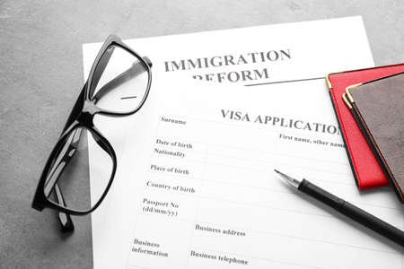 Passports, glasses and visa application form on table. Immigration reform Stock Photo