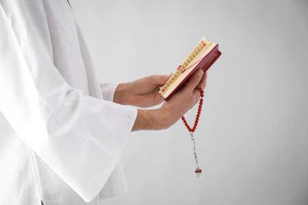 Young Muslim man reading Koran on light background Stock Photo