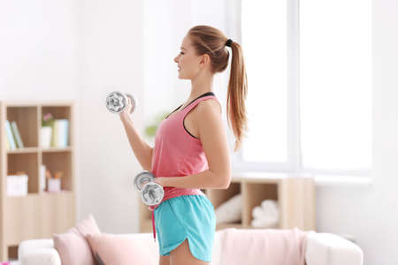 Beautiful young woman doing fitness exercise with dumbbells at home