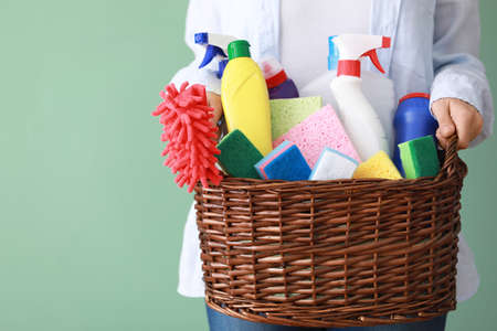 Woman holding basket with cleaning supplies on grey background