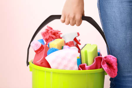Woman holding bucket with cleaning supplies on color background Stock Photo