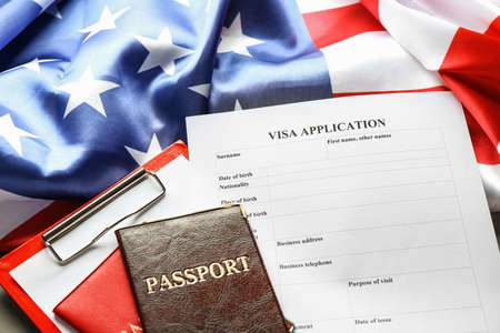 Passports, American flag and visa application form on table. Immigration to USA