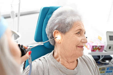 Otolaryngologist examining senior womans ear with ENT telescope in hospital. Hearing problem