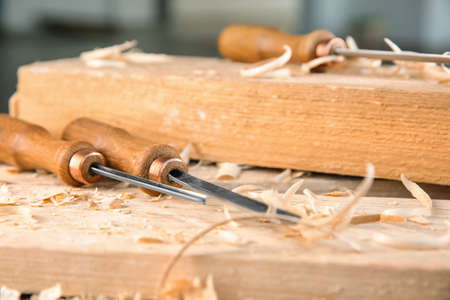 Chisels, wooden boards and sawdust in carpenters workshop