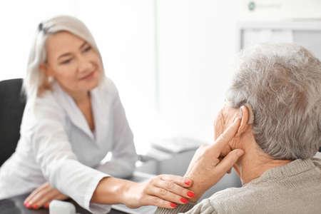 Senior woman adjusting hearing aid in doctors office