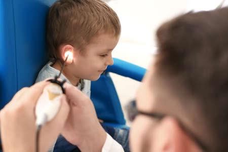Otolaryngologist examining little boys ear with ENT telescope in hospital. Hearing problem