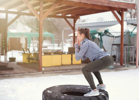 Young muscular woman training on heavy tire, outdoors Stock Photo