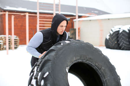 Young muscular man flipping heavy tire, outdoors