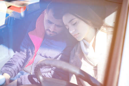 Young couple sleeping in car during traffic jam