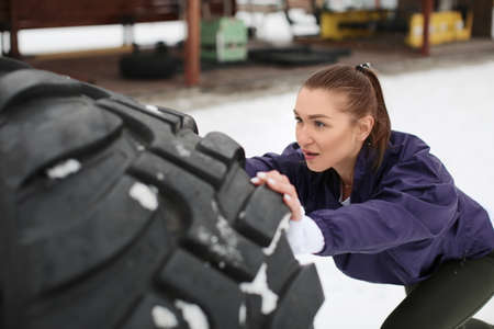 Young sporty woman flipping heavy tire, outdoors