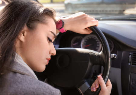 Young woman sleeping in car during traffic jam