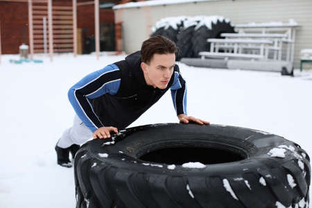 Young muscular man training on heavy tire, outdoors