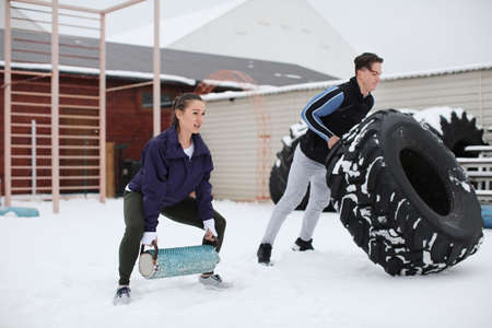 Young sporty woman and man training with heavy tire, outdoors Stock Photo