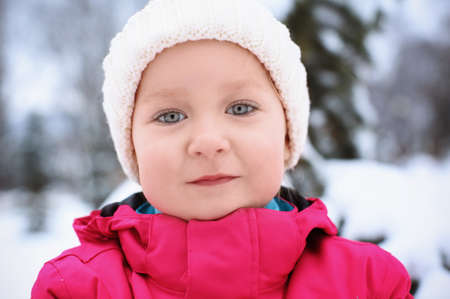 Cute little girl in snowy park on winter vacation