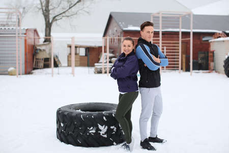Young sporty woman and man with heavy tire, outdoors Stock Photo