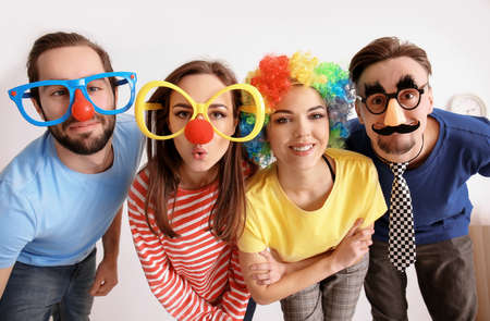 Young friends in funny disguise posing on light background. April fool's day celebration
