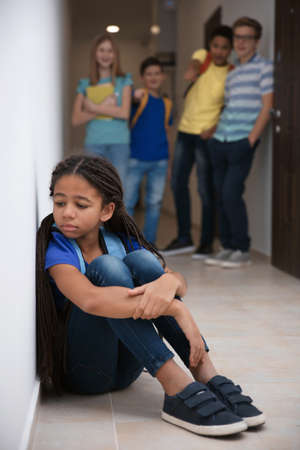 Sad African American girl indoors. Bullying in school