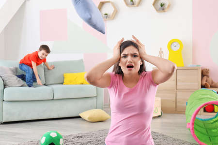 Young nanny in despair and troublesome child at home Stock Photo