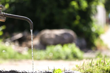 Tap with pouring water outdoors. Water scarcity concept