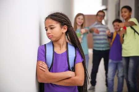 Sad African American girl indoors. Bullying in school