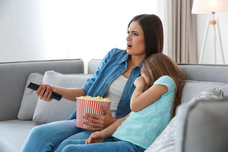 Young woman watching TV with her daughter on sofa at home