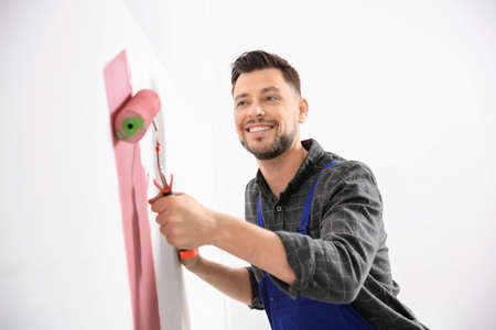Young male decorator painting wall in room