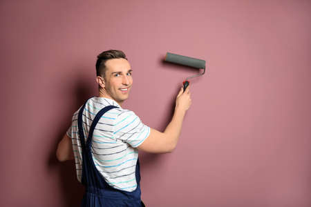 Young male decorator with paint roller near color wall Stock Photo