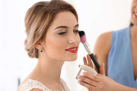 Artista di trucco che prepara sposa prima del suo matrimonio