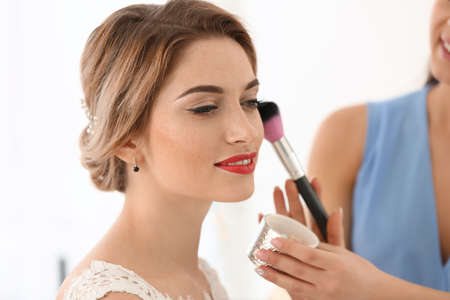 Makeup artist preparing bride before her wedding